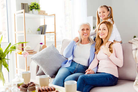 Retirement motherhood maternity parenthood birthday happiness care trust support people concept. Cheerful excited glad emotional with toothy smile women sitting on sofa spending time together Фото со стока