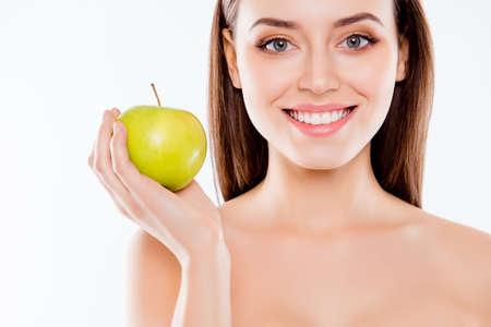 クリアクリア強い健康なストレート歯の胃の概念。白い背景に孤立した手に緑の新鮮なリンゴを示す美しい魅力的な女性のクローズアップポートレ