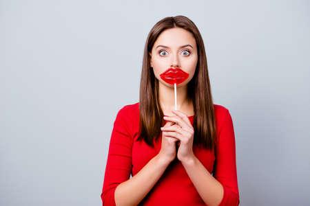 Charmante, mooie, verraste donkerbruine dame wil lippen hebben als een lolly, bonbon op stok bij mond houden, met wijd open ogen, staande over grijze achtergrond Stockfoto