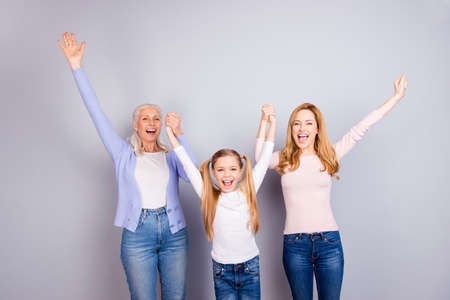 Wow hooray yes yeah! Motherhood maternity parenthood triumph victory sward family concept. Cute lovely adorable delightful relatives raising hands up jeans casual isolated on gray background