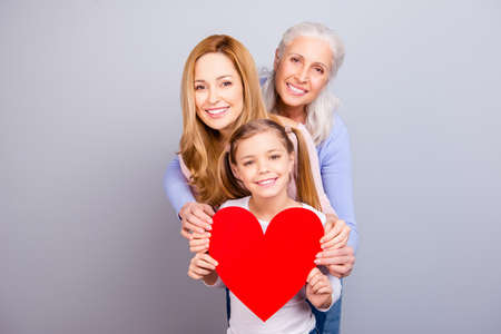 Motherhood relationship maternity loveliness tenderness cute blonde-haired parenthood generation concept. Beautiful cheerful excited granny mom kid holding one big heart isolated on gray background