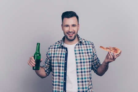 Portrait of cheerful joyful bearded brunet guy in checkered shirt holding slice of pizza and bottle of beer, ready to watch football match, no diet on holidays, standing over grey background