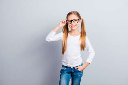 Beauty positivity emotional expressing blonde hair dream profession occupation concept. Portrait of beautiful adorable dreamy girl touching glasses keeping hand in pocket isolated on gray background