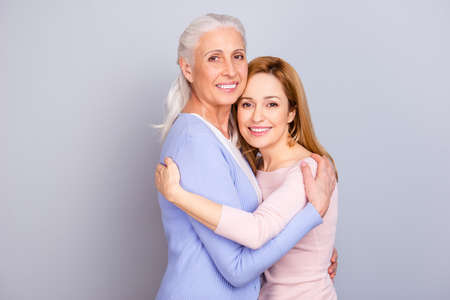Grandparent maternity friendship touching relatives concept. Portrait of cheerful cute lovely sweet beautiful mommy and adult daughter isolated on gray background copy-space