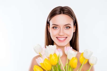 Wellness vitality womanhood no plastic surgery concept. Close up portrait of attractive gorgeous woman with pure ideal flawless smooth sensitive skin holding yellow white tulips isolated on background