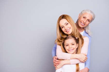 魅力的な美しい友好的な王支持かわいい家族の肖像画は、灰色の背景コピースペースに孤立したお互いを抱きしめる