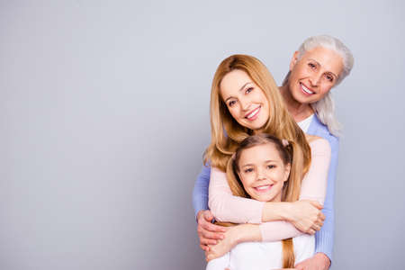 Portrait of charming beautiful friendly king supportive cute family members hugging each other isolated on gray background copyspace Фото со стока