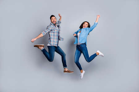 Él contra Ella, retrato de cuerpo entero de una pareja atractiva, juguetona, alegre y cómica en atuendo casual, jeans, camisas saltando sobre un fondo gris.
