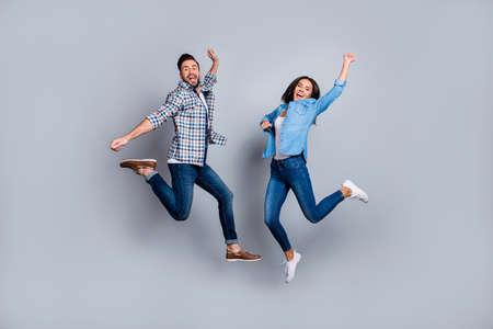 He vs She ritratto a figura intera di coppia attraente, giocosa, allegra, comica in abito casual, jeans, camicie che saltano su sfondo grigio