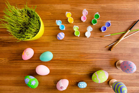 Top view portrait with copy space for text of easter objects on wooden brown background laying painted eggs, flower, paints and tassels Stock Photo