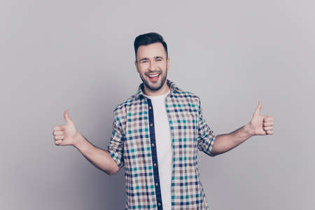 Portrait of smiling, bearded, brunet, cool man gesturing two thumbs up in checkered shirt over grey background, approving, recommend, like new product Stock Photo