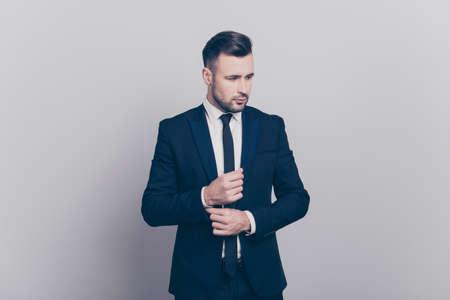青いジャケットの若いスタイリッシュなディレクターの肖像画は、灰色の背景の上に側面を見て彼の白いシャツのカフリンクスにボタンを固定します 写真素材 - 94040753