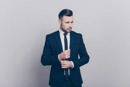 Portrait of young attractive  stylish director in blue jacket fixing buttons on cufflinks of his white  shirt looking to the side over grey background Фото со стока