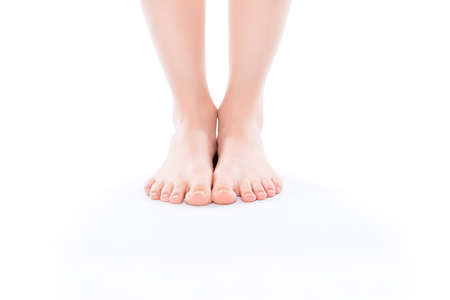 Cosmetics illness medicine vitality wellness size concept. Cropped close up photo of ideal perfect beautiful attractive woman's bare foot standing on white floor isolated on background copy-space Stockfoto