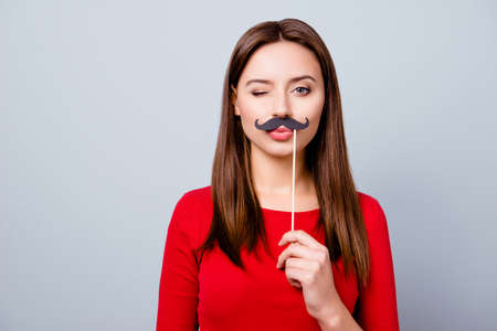 Portrait with empty copy space for text of cool pretty charming crazy girl holding black paper party mustache on stick, winking with pout lips, standing over gray background