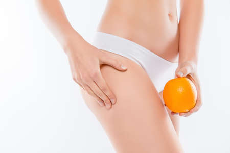 Vitamins vegan lifting sedentary stretch concept. Cropped close up photo of womans hand holding orange compare showing peel with ideal perfect smooth flawless skin on hips isolated, white background Stock Photo