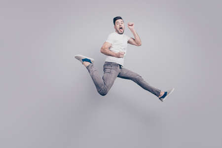 Happiness, freedom, motion and people concept. Shocked, funky, handsome man jumping in air, screaming, shouting with open mouth over grey background Stock Photo