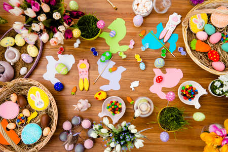 Top view of  of easter composition with chocolate, colored eggs, papper rabits, gingerbread, flowers, dragee, tassels, paints on wooden background Stock Photo