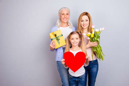 Positivity beauty care trust tenderness concept. Three family sweet cute adorable loving members holding heard package and beautiful flowers cuddling standing together isolated on gray background