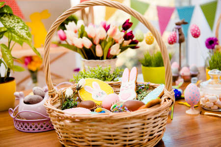 Close up portrait of wooden basket with easter composition, sweets, choco, gingerbread standing on table over decorative background