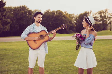 Cute sweet partners on a date outside, well dressed, excited, lovely. Good day, happiness, friendship concept. Lady holds present, guitarist plays instrument and sings Stock Photo