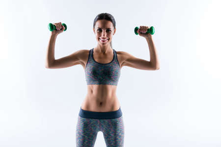 I am strong and healthy! Beautiful attractive charming sportive flexible young woman dressed in sport wear, she is pushing up dumbbells up to build muscles, isolated on white background