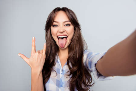 Self portrait of nice, attractive, crazy woman, shooting selfie and showing rock and roll symbol with tongue out to the front camera over grey background Stock Photo