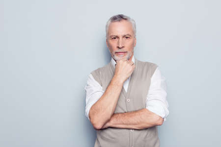 Close up portrait of qualified serious strict pensive clever head on big company thinking over new start-up in his business rolled-up sleeves white shirt beige waistcoat isolated on gray background