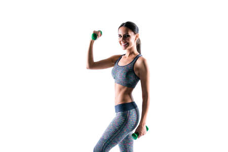 Attractive beautiful sporty healthy woman wearing tight clothes is doing exercises using dumbbells, isolated on white background