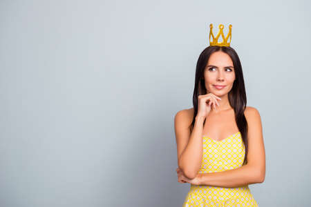 Beautiful charming attractive cute lovely tender pensive with long straight hair woman wearing dotted yellow dress and golden crown is planning how to become famous, isolated on grey background