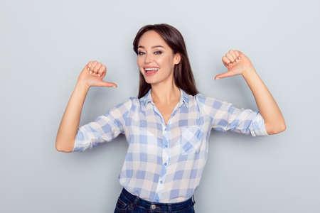 C'est moi! Portrait of smiling cheerful nice jeune femme en chemise à carreaux pointant les doigts du pouce sur son corps isolé sur fond gris, fier d'elle-même, ayant l'ego Banque d'images - 95294909