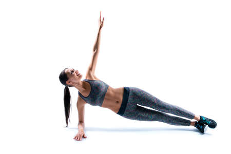 I want to feel like a million dollars! I do all my best to be healthy! Side profile view of purposeful attractive wearing tight pans and top sport woman doing plank, isolated on white background