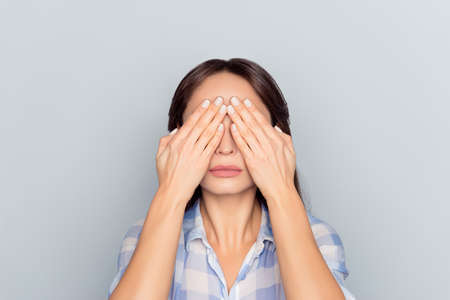 Close up portrait of tired woman after long working day on computer having eye problem, pressure, covering face, eyes with hands, afraid to look, standing over grey background