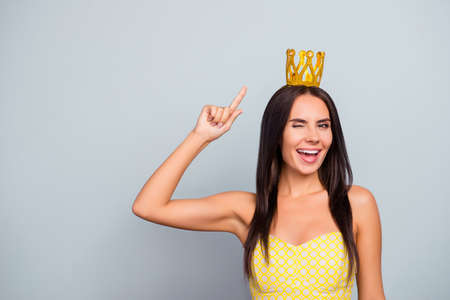 Im queen of beauty! Where are my servants? Cheerful beautiful attractive pretty charming woman is pointing on the golden crown on her head and giving a wink, isolated on grey background, copy-space Stok Fotoğraf