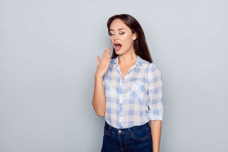 Portrait of tired, bored, nice, attractive woman in checkered shirt, closing her open mouth, she wants to sleep, yawning over grey background
