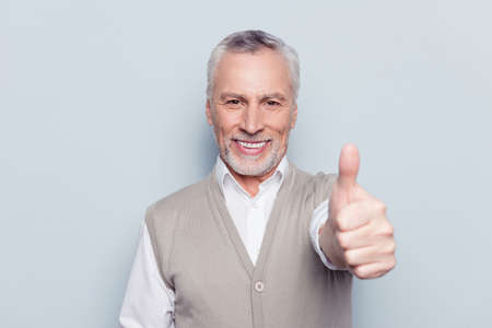 Well done! Close up portrait of delightful confident cool glad pleased cheerful excited grandpa demonstrating thumb-up knitted beige waistcoat beaming smile isolated on gray background
