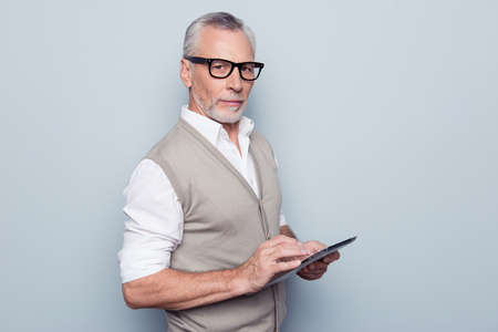 Modern technology leadership people concept. Half-turned portrait of authoritative respectful proud leader man using digital gadget at workplace rolled-up shirt sleeves isolated on gray background Foto de archivo