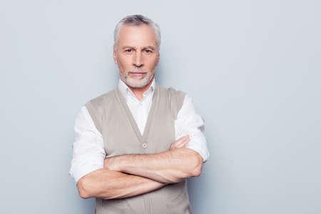 Concept de mode de vie individuel de personnes. Portrait de grand-père pensif auto-assuré sérieux sérieux viril avec les mains croisées gilet tricoté beige isolé sur fond gris copy-space
