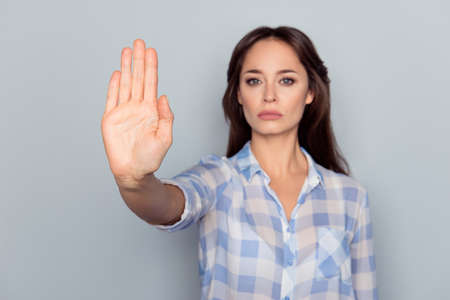 Prohibition symbol. Closeup portrait of young, serious, pretty, charming girl in checkered shirt making stop gesture with palm of her hand on grey background