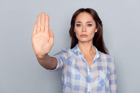Verbod symbool. Close-upportret van jong, ernstig, mooi, charmant meisje die in geruit overhemd eindegebaar met palm van haar hand op grijze achtergrond maken