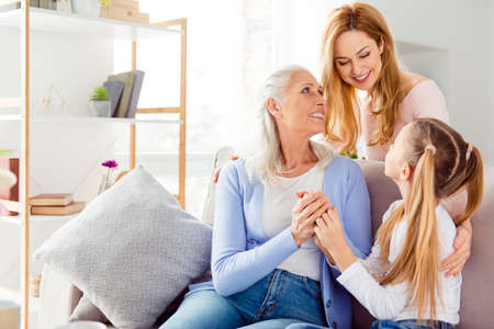 Parenthood tender gentle help aid maternity celebration comfort concept. Three cute cheerful excited sweet delightful beautiful mom mum mommy granny schoolgirl spending time together sitting on sofa