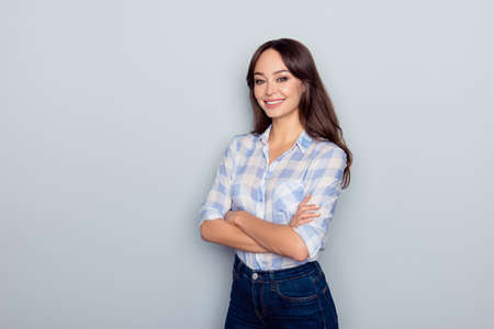 Portrait with copy space of ideal cute woman with beaming smile in checkered shirt, having her hands crossed, standing over grey background