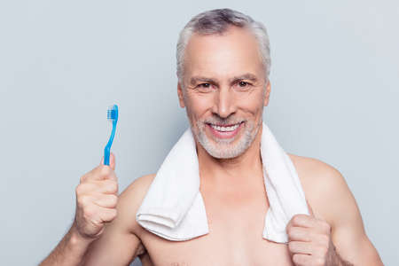 False fake teeth care concept. Close up portrait of cheerful excited glad pleased with shiny beaming toothy smile grandpa using blue toothbrush towel on shoulders isolated on gray background Stock Photo
