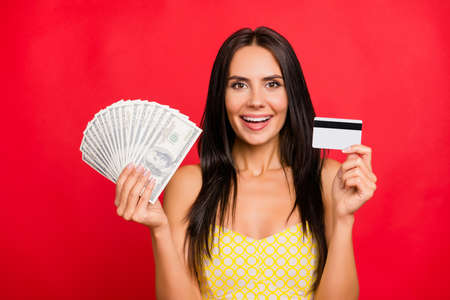 Look what I have! Close up portrait of cheerful joyful beautiful with long dark hair boasting about earnings on the internet, withdraw money, isolated on red background Archivio Fotografico