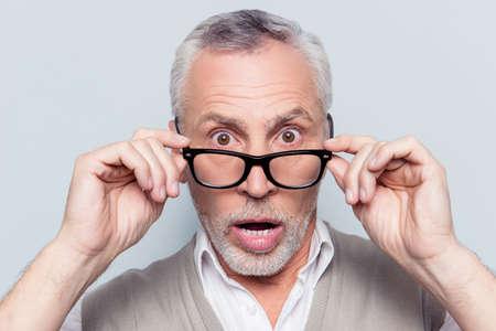 Nehmen Sie die Brille ab. Bist du verrückt? Schließen Sie herauf Porträt des entsetzten überraschten unsicheren unassured erschrockenen Großvaters, der das rim-glassed pop-eyed Schauen lokalisiert auf grauem Hintergrund berührt