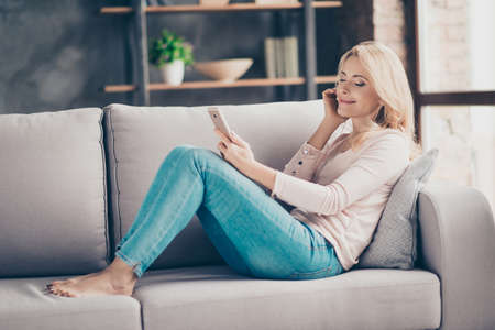 Full length portrait of charming pretty woman in jeans and pullover siting with legs on couch in livingroom, having earphones, using, holding smart phone, listening music with close eyes