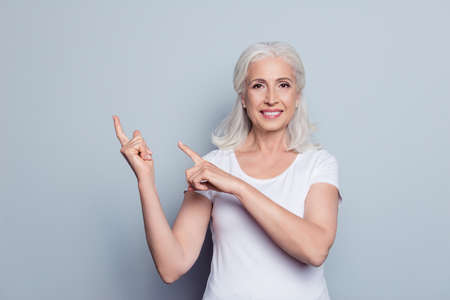 Portrait of perfect, nice, old, smiling woman in t-shirt demonstrate, choosing, pointing with two forefingers to copy space, looking at camera, standing over gray background