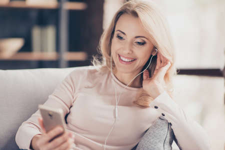 Close up portrait of attractive pretty woman  siting on couch in living room, having, using earphones, holding smart phone, listening music, looking at screen of telephone in hand Foto de archivo