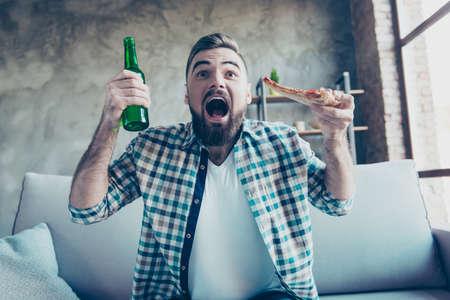 幸せな興奮の肖像画は、カジュアルな服を着て陽気なひげを生やした男を驚かせ、彼はテレビを見て、彼のお気に入りのサッカーチームをサポートしています 写真素材 - 95427349