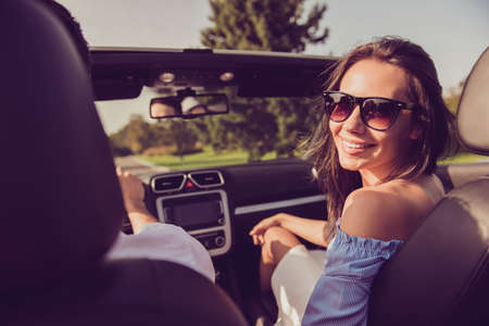 Carefree gorgeous cheerful lady wife turn for shot, back view of driver husband, on their way to honeymoon. Feelings, married family, friendship, reach destination, escape, speed ride, relax lifestyle Stockfoto - 95427352
